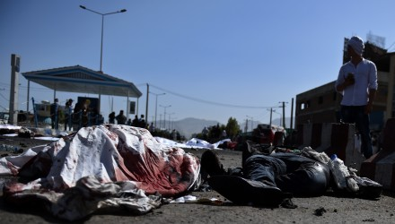 An Afghan protester stands near the bodies of victims at the scene of a suicide attack that targeted crowds of minority Shiite Hazaras during a demonstration at the Deh Mazang Circle of Kabul on July 23, 2016. Islamic State jihadists claimed responsibility for twin explosions  July 23 that ripped through crowds of Shiite Hazaras in Kabul, killing at least 61 people and wounding 207 others in apparently their deadliest attack in the Afghan capital. The bombings during a huge protest over a power transmission line could deepen sectarian divisions in a country well known for communal harmony despite decades of war.  / AFP PHOTO / WAKIL KOHSAR