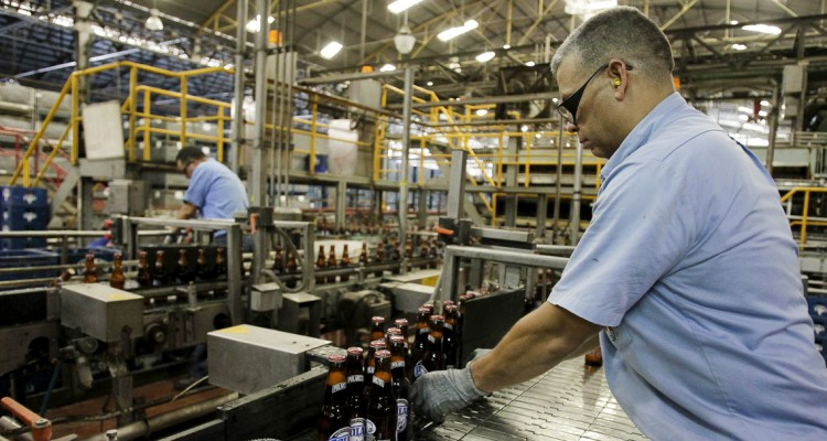 Employees work at a production line in Polar brewery in Maracaibo, Venezuela July 13, 2015. Venezuela's Labor Ministry has ordered workers to lift a strike at beer maker Polar that had halted two of its breweries and restricted supplies of beer in the South American nation. Polar, the country's largest privately owned company, produces as much as 80 percent of the beer consumed in the country, which has historically been among the world's top per capita consumers of beer. Picture taken on July 13, 2015. REUTERS/Isaac Urrutia