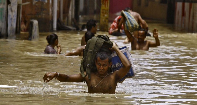 Flood-affected people carry their belongings as they move to safer grounds along a flooded street at West Midnapore district in West Bengal, India, August 4, 2015. At least 75 people have died and tens of thousands have had to take refuge in state-run relief camps after heavy rains caused floods and landslides in eastern India, government officials and aid groups said on Monday. REUTERS/Rupak De Chowdhuri