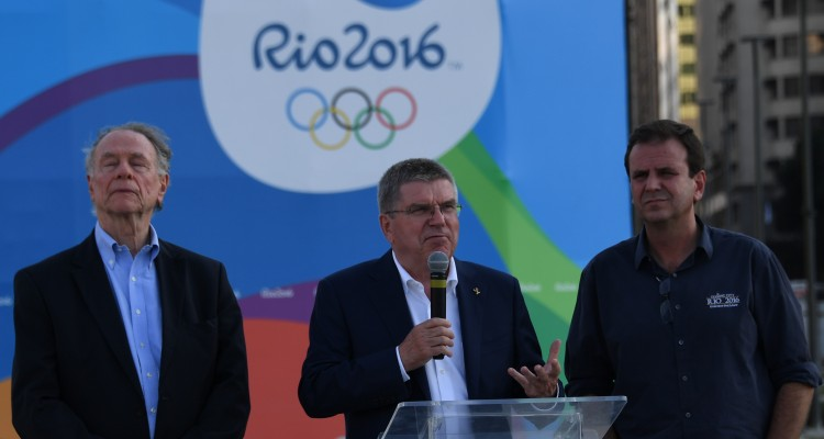 The President of the International Olympic Committee (IOC) Thomas Bach (C), accompanied by Rio de Janeiro's Mayor Eduardo Paes (R) and the President of the Local Organising Committee, speaks during a visit at the place where the Olympic flame will light in the Boulevard de la Orla, in front of Guanabara Bay in Rio de Janeiro on July 27, 2016.   / AFP PHOTO / VANDERLEI ALMEIDA