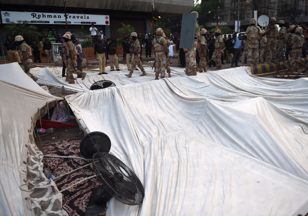 Pakistani paramilitary rangers stand over a demolished hunger strike camp of the Muttahida Qaumi Movement (MQM) political party following a clash with police in Karachi on August 22, 2016.  Activists of a key political party clashed with police and ransacked a private television station in the southern Pakistani port city of Karachi, leaving at least one man dead and seven others injured. / AFP PHOTO / ASIF HASSAN