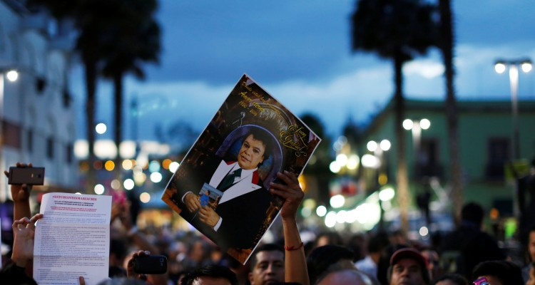 A fan holds a picture of late Mexican singer Juan Gabriel during a mass in his honor at Plaza Garibaldi, in Mexico City, Mexico