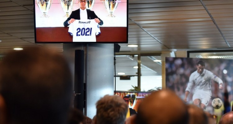 People watch a TV before the official presentation of Real Madrid's Portuguese forward Cristiano Ronaldo's contract renewal, in the presidential box at the Santiago Bernabeu stadium in Madrid on November 7, 2016.  Real Madrid and Cristiano Ronaldo have agreed an extension to the player's contract, keeping him at the club until the 30th of June 2021. / AFP PHOTO / GERARD JULIEN