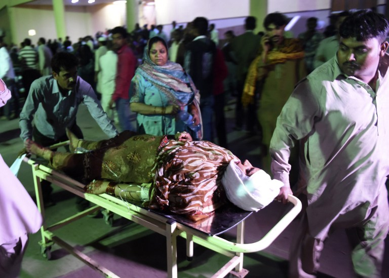 Pakistani rescuers transport an injured woman to a hospital in Karachi on November 12, 2016, following a suicide bombing at a Sufi shrine. At least 52 people died and more than 100 others were injured November 12 in a bomb blast at a remote Sufi shrine in Pakistan, officials said, with the Islamic State group claiming the attack. The blast hit worshippers participating in a ceremony at the shrine of the Sufi saint Shah Noorani, some 750 kilometres (460 miles) south of Quetta, the provincial capital of restive southern Balochistan province.  / AFP PHOTO / RIZWAN TABASSUM